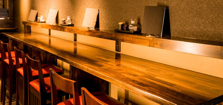 賛SUN大宮本店。木製カウンターと椅子6脚が温かみのある照明に照らされた店内の画像です。